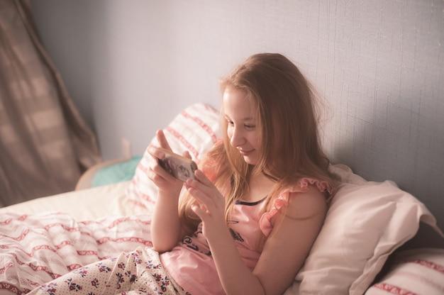 De tiener ligt op bed inmorning zon en het kijken