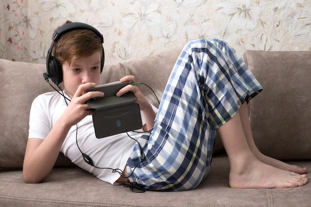 De tiener ligt op grijze bank met hoofdtelefoons en speelt videospelletjes op de telefoon