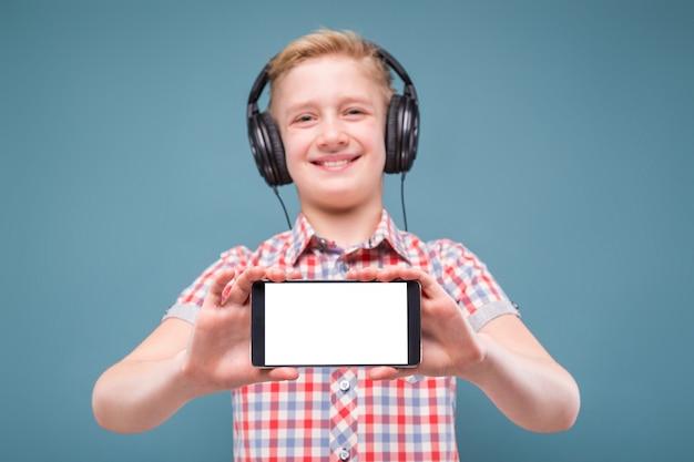 De tiener met hoofdtelefoons toont smartphonevertoning