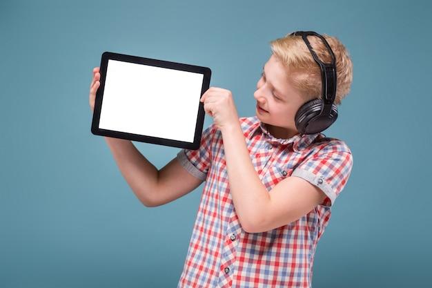 De tiener met hoofdtelefoons toont tabletvertoning, foto met ruimte voor tekst