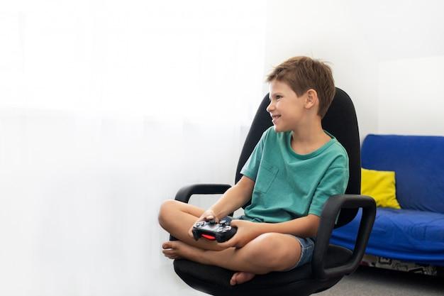 De tiener speelt een computerspel met hoofdtelefoons en een joystick, spelconsole.