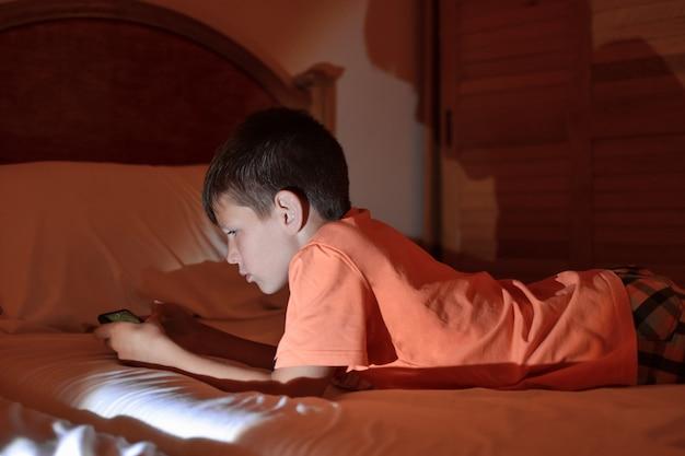 De tiener speelt een spelletje op een mobiele telefoon terwijl hij ontspant in een hotelkamer