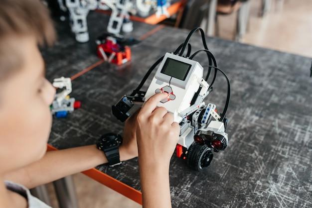 De tiener speelt met de robot aan de tafel.