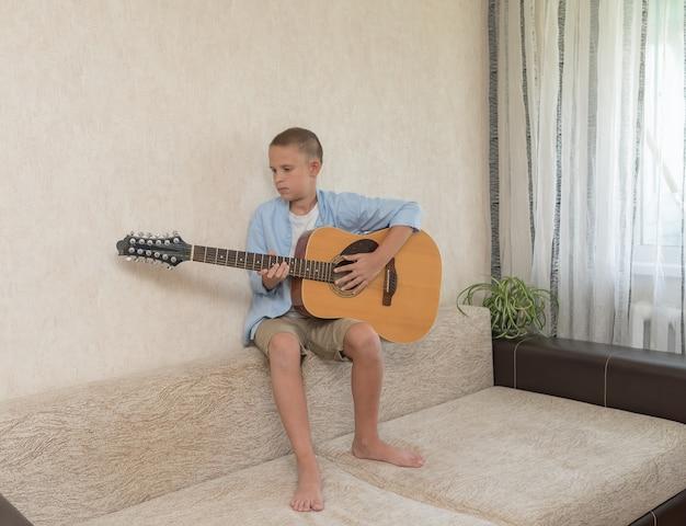 De tiener speelt thuis in zijn eentje gitaar.