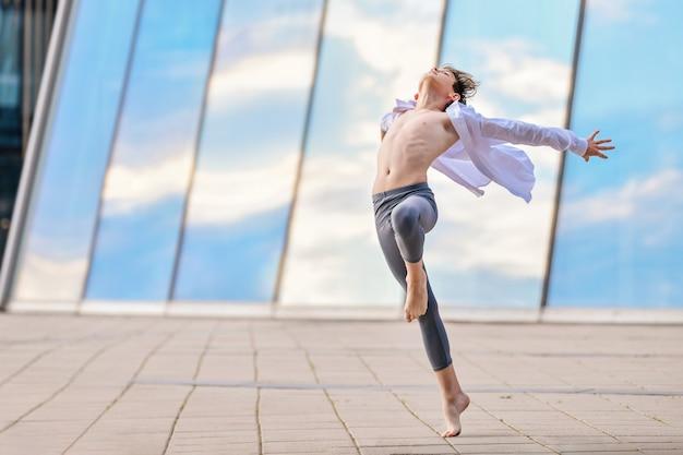 De tiener van de balletjongen danst expressief tegen de achtergrond van de luchtreflectie in de glazen wand