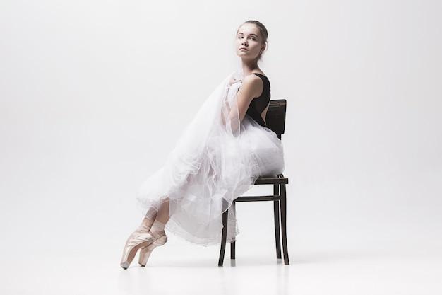 De tienerballerina in wit pak zittend op een stoel