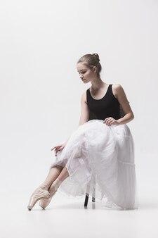 De tienerballerina in witte pakzitting op stoel