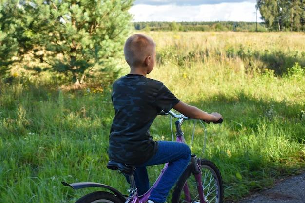De tienerjongen berijdt een fiets in het bos