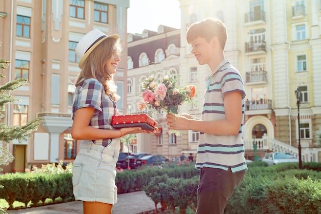 De tienerjongen feliciteert meisje met boeket van bloemen en gift