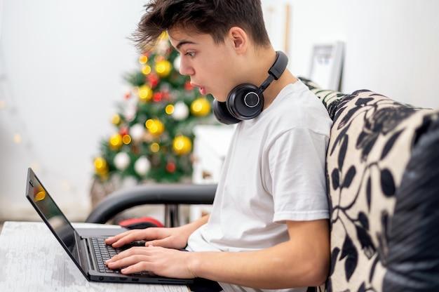 De tienerjongen gebruikt thuis laptop met hoofdtelefoons. kerstboom aan de muur. verbaasd gezicht