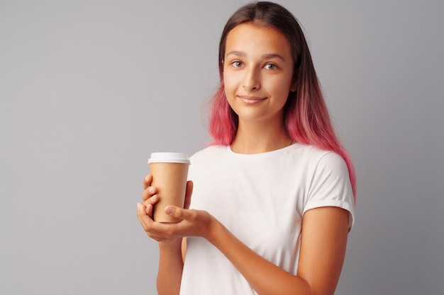 De tienermeisje dat van nice een kop van koffie over een grijze achtergrond houdt