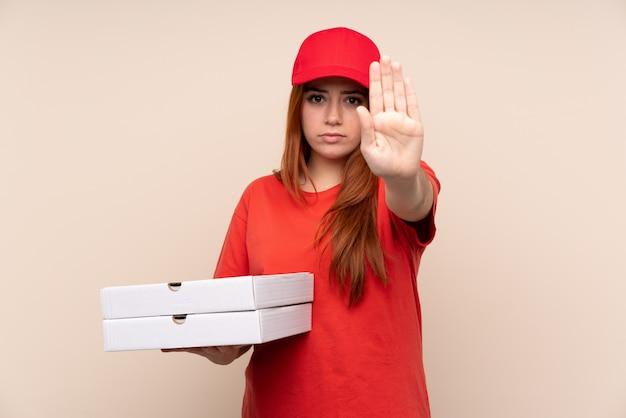 De tienermeisje die van de pizzakoerier een pizza over geïsoleerde muur houden die eindegebaar met haar hand maken