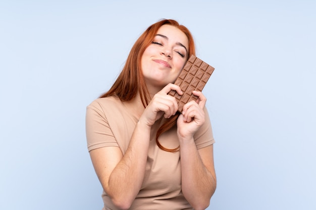 De tienermeisje van de roodharige over geïsoleerde blauwe muur die een chocoladetablet neemt en gelukkig
