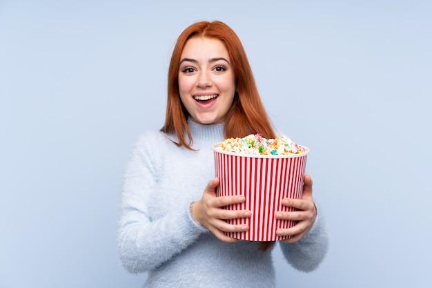 De tienermeisje van de roodharige over geïsoleerde blauwe muur die een grote emmer popcorns houdt