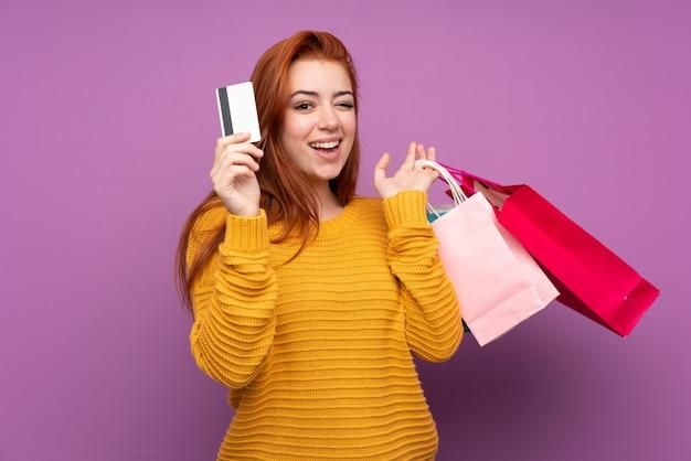 De tienermeisje van de roodharige over geïsoleerde purpere muurholding het winkelen zakken en een creditcard