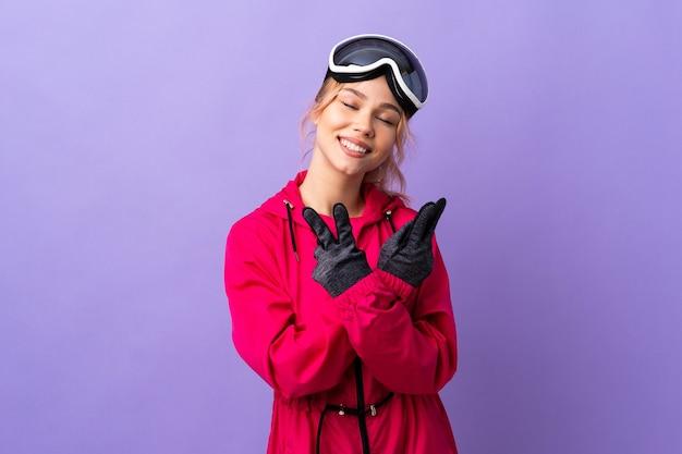 De tienermeisje van de skiër met snowboardbril over geïsoleerde purpere muur die en overwinningsteken glimlacht toont
