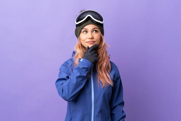De tienermeisje van de skiër met snowboardglazen over geïsoleerde purpere muur die een idee denken terwijl omhoog het kijken