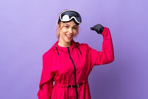 De tienermeisje van de skiër met snowboardglazen over geïsoleerde purpere muur die een overwinning viert