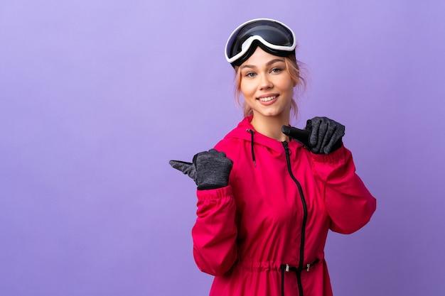 De tienermeisje van de skiër met snowboardglazen over geïsoleerde purpere muur die naar de kant richt om een product te presenteren