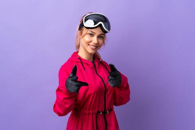 De tienermeisje van de skiër met snowboardglazen over geïsoleerde purpere muur die naar voren wijst en glimlacht