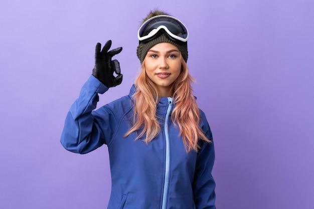 De tienermeisje van de skiër met snowboardglazen over geïsoleerde purpere muur die ok teken met vingers tonen