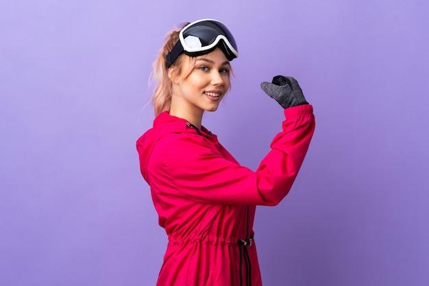 De tienermeisje van de skiër met snowboardglazen over geïsoleerde purpere muur die sterk gebaar doet