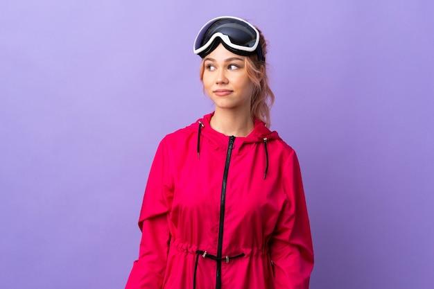 De tienermeisje van de skiër met snowboardglazen over geïsoleerde purpere muur die twijfelsgebaar maken kijkend kant