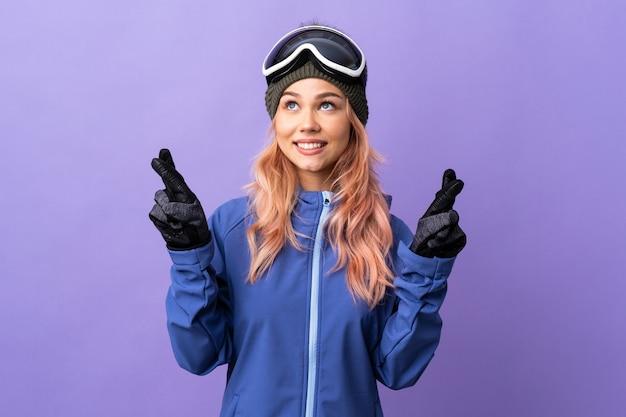 De tienermeisje van de skiër met snowboardglazen over geïsoleerde purpere muur met en het beste wensen van vingers