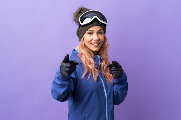 De tienermeisje van de skiër met snowboardglazen over geïsoleerde purpere verraste en wijzende muur voorzijde