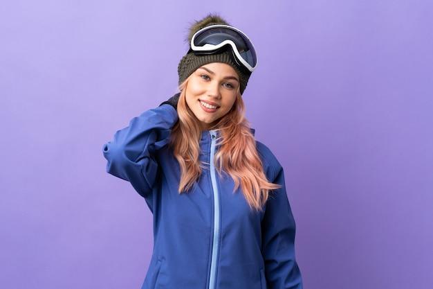 De tienermeisje van de skiër met snowboardglazen over het geïsoleerde purpere muur lachen