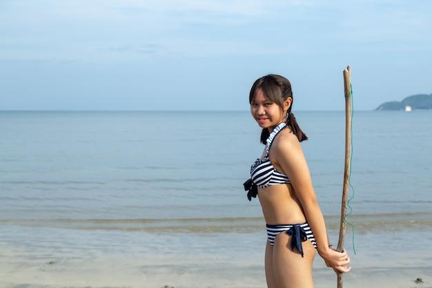 De tienermeisjes die van azië bikini dragen bij het strand met exemplaarruimte.