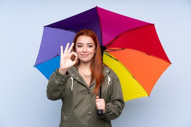 De tienervrouw die van de roodharige een paraplu over geïsoleerde blauwe muur houdt die een ok teken met vingers toont