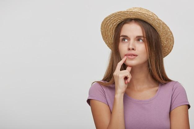 De tienervrouw in een strohoed met een roze lint kijkt verbaasd opzij en probeert zich iets belangrijks te herinneren
