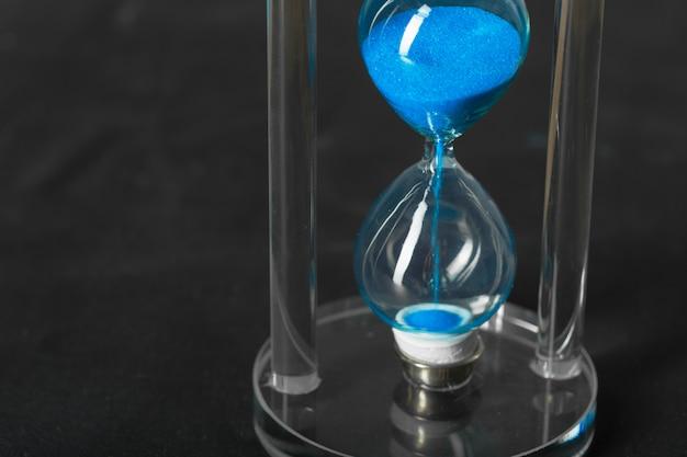 De tijd gaat voorbij blauwe zandloper dicht omhoog
