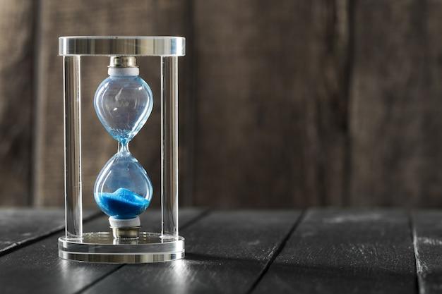 De tijd gaat voorbij. blauwe zandloper dichte omhooggaand