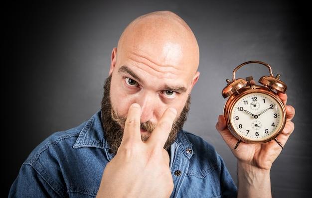 De tijd loopt door. man kijkt naar klok. bebaarde man met klok.