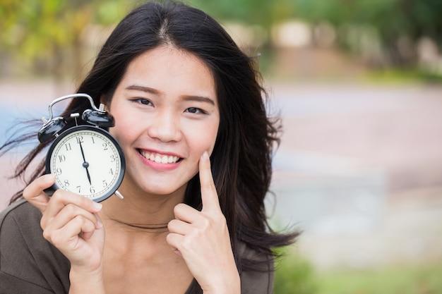 De tijd van het babygezicht, leeftijdloos leuk aziatisch vrouwenmeisje met jonge huid kijkt met kloktijd