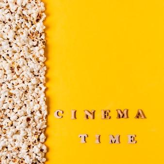 De tijdtekst van de bioskoop dichtbij popcorns op gele achtergrond