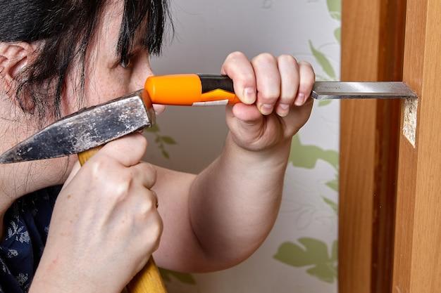 De timmerman beitelt zodat de voorkant van de grendel in hout wordt verzonken.