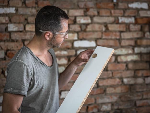 De timmerman evalueert het boorresultaat in de plank