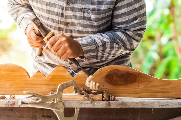 De timmerman gebruikt beitels en hamers om te kerven