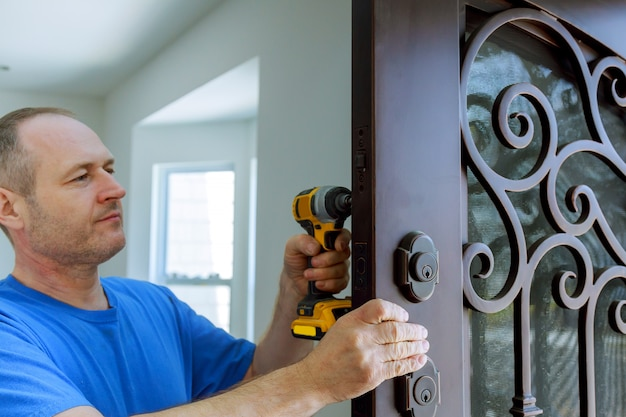 De timmerman installeert een betrouwbare resistente vergrendeling in de metalen deur.