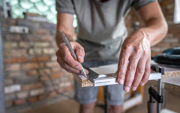 De timmerman meet het hout met een hoekgereedschap en maakt aantekeningen.
