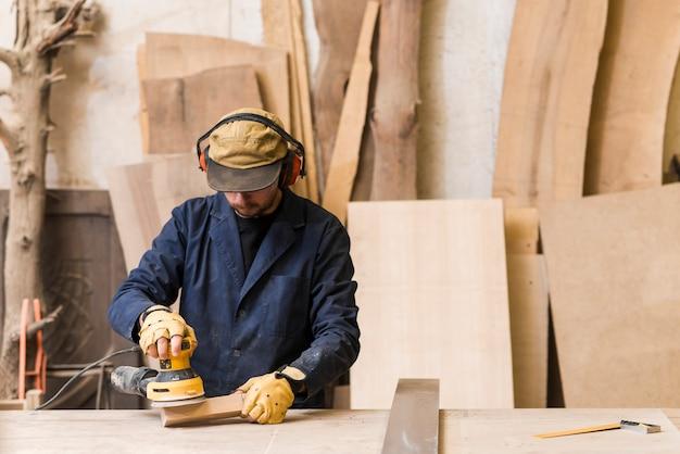 De timmerman polijst houten raad met een willekeurige baanschuurmachine in de workshop