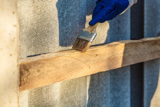 De timmerman verft een houten plank met een kwast in zijn hand met een bijtende verf