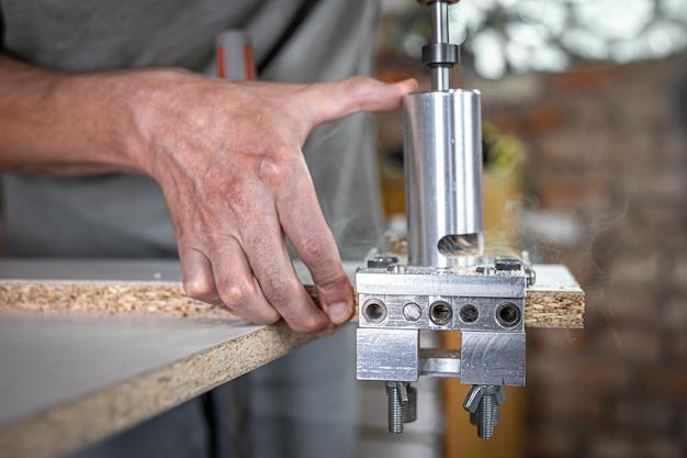 De timmerman werkt als een professioneel gereedschap voor het boren van hout.