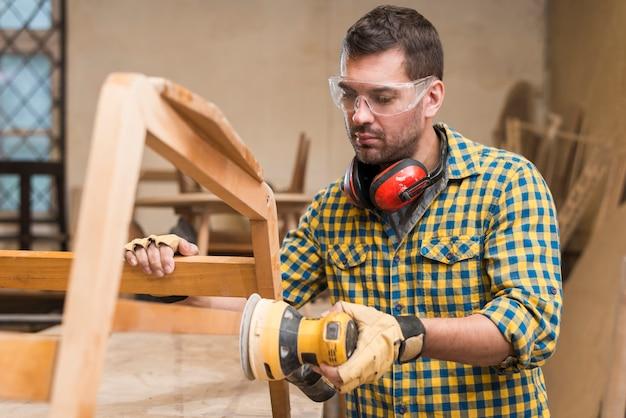 De timmerman werkt met de elektrische polijstmachine op het hout