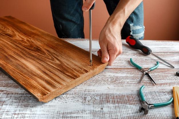 De timmerman werkt met hout op zijn werkruimte