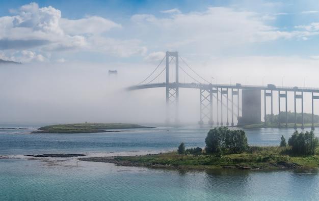 De tjeldsund-brug in de mist. de brug verbindt het eiland hinnoya met het vasteland, noorwegen
