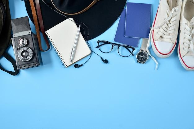 De toebehoren van de reiziger op blauwe achtergrond met hoed, rugzak, oogglazen, paspoort, schoenen en blocnote.